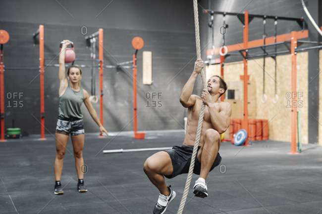 Young man exercising with rope while girlfriend lifting kettlebell in gym