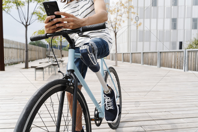 Low section of man with artificial limb using mobile phone on bicycle in city