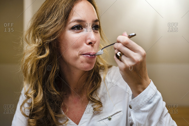Businesswoman looking away while eating food with spoon