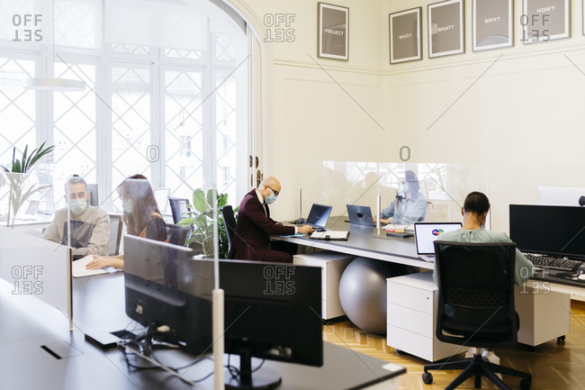 Business professionals with protective mask working at desk in office