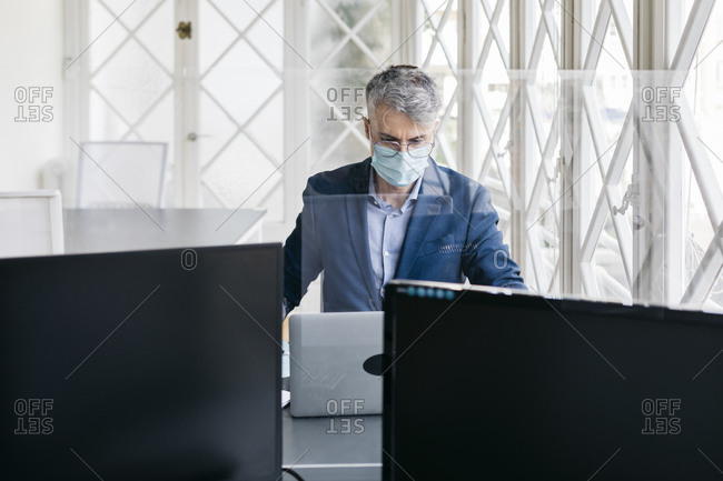 Male entrepreneur with protective mask working on laptop in office seen through glass division