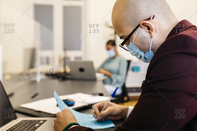 Businessman with safety mask writing while working at office desk