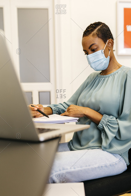 African businesswoman with safety mask reading papers while sitting in office