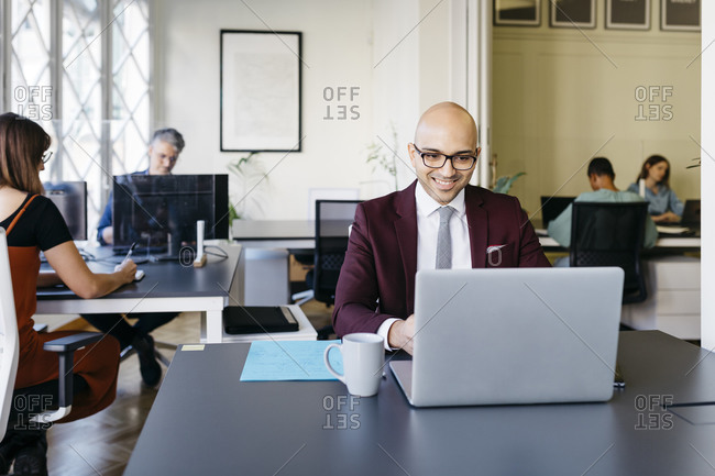 Smiling bald businessman working on laptop at desk in office