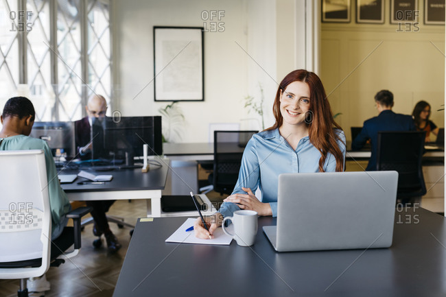 Smiling businesswoman writing in paper at office desk
