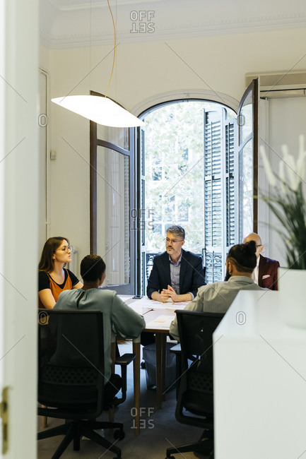 Businessmen and businesswomen discussing at table in office seen through doorway