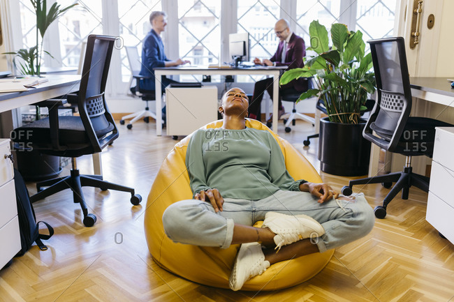 Tired businesswoman with eyes closed resting on bean bag in office