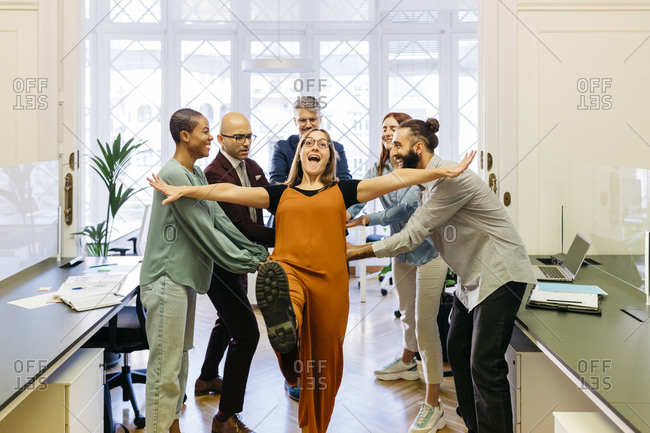 Cheerful businesswoman falling while coworkers catching at workplace