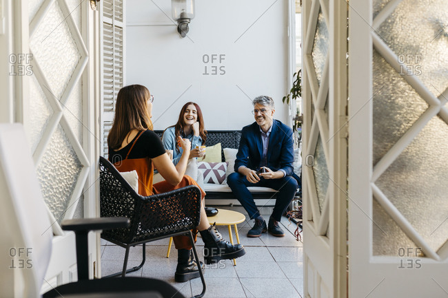 Smiling female entrepreneur discussing with coworkers while having coffee on sofa in balcony