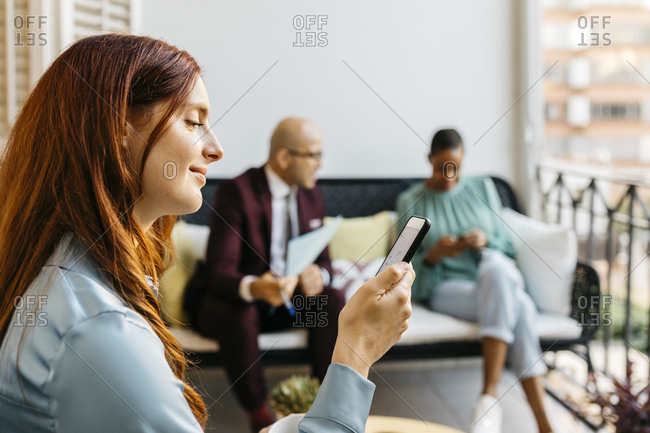 Smiling businesswoman using smart phone while coworkers sitting in balcony