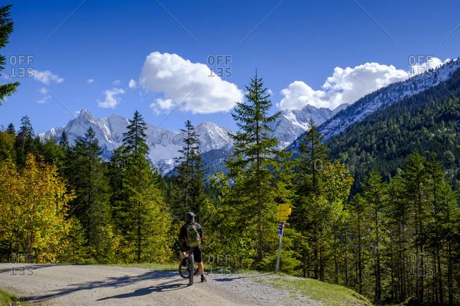 Male biker admiring forested Gleirschtal valley in summer