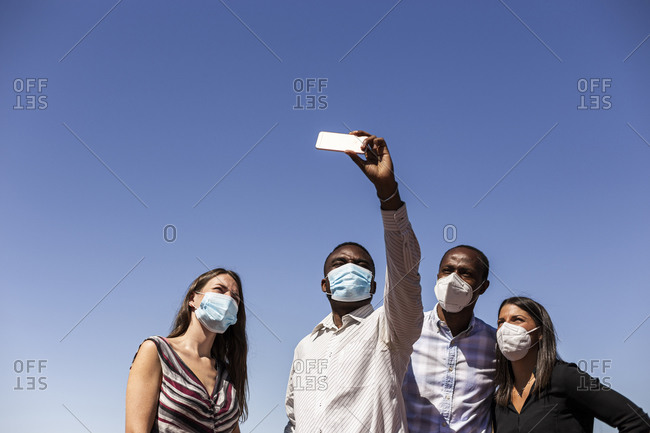 Business professionals taking selfie with protective face masks against clear blue sky on sunny day