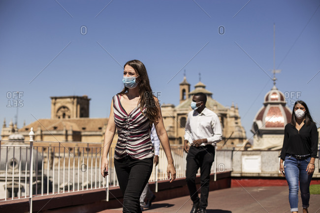 Business people wearing masks while walking at rooftop of office building
