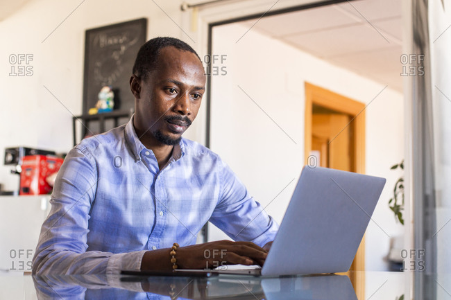 Serious businessman using laptop at table in coworking office