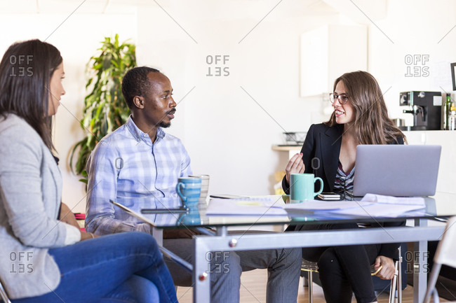 Multi-ethnic male and female colleagues discussing during meeting in coworking office