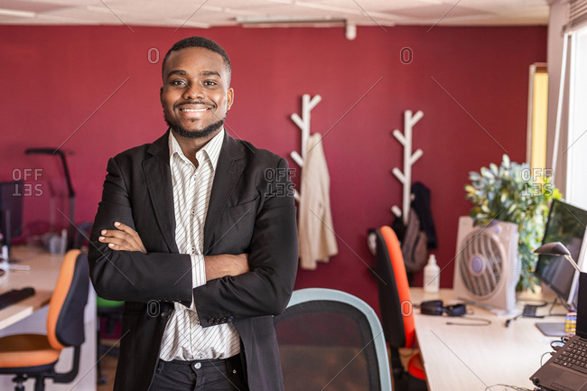 Confident businessman standing with arms crossed in coworking office
