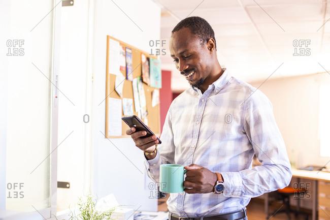 Smiling businessman using smartphone during coffee break