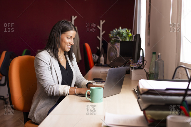 Smiling businesswoman using laptop at desk in coworking office