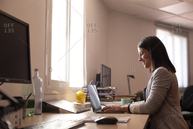 Smiling female business professional using laptop in coworking office