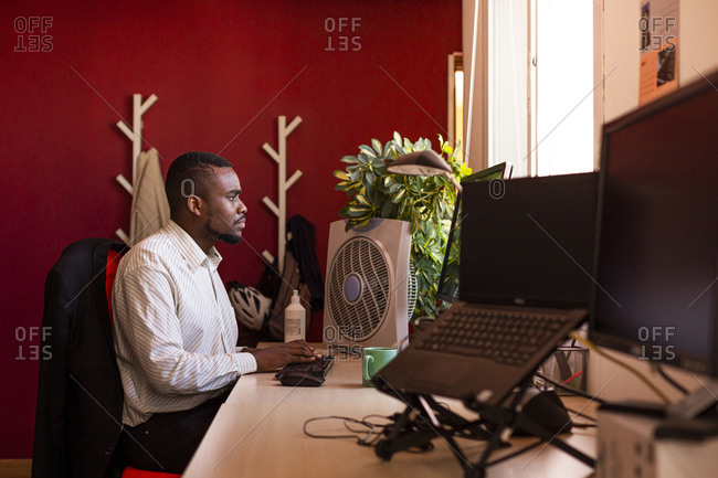 Focused young businessman using computer at desk in coworking office