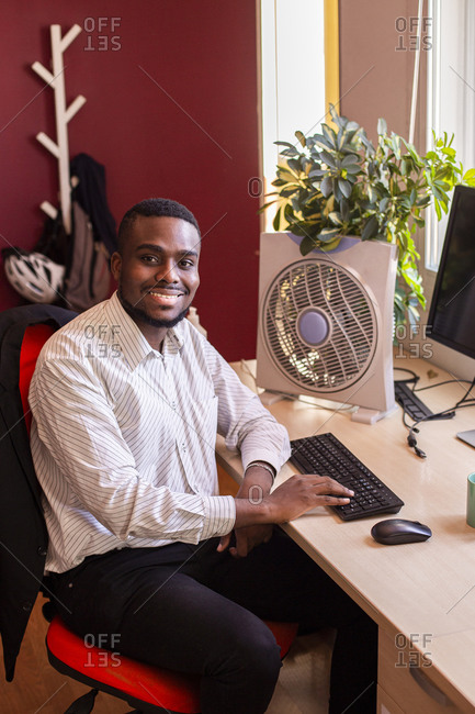 Smiling young businessman using computer at desk in office