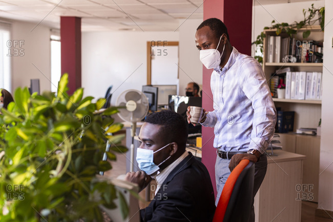 Male business professionals in protective face masks working at office during COVID-19 crisis