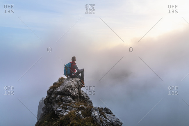 Pensive male hiker sitting on mountain peak during sunrise at Bergamasque Alps- Italy