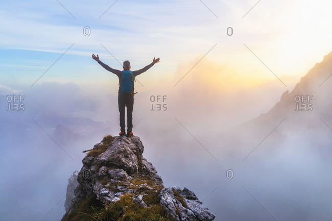 Pensive male hiker with arms outstretched standing on mountain peak during sunrise at Bergamasque Alps- Italy