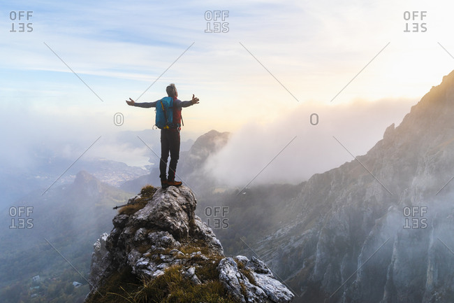 Pensive hiker with arms outstretched standing on mountain peak during sunrise at Bergamasque Alps- Italy