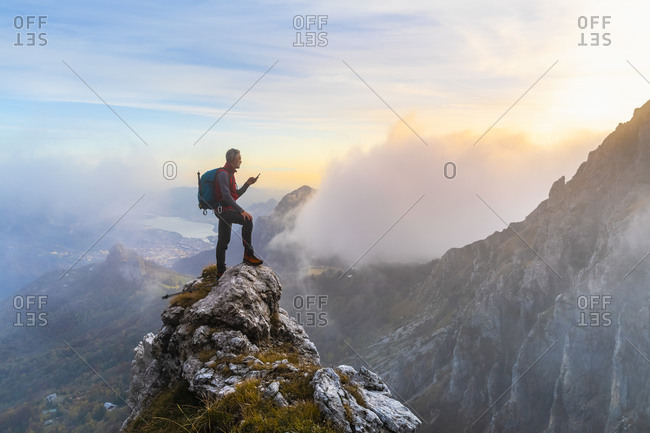 Pensive hiker using smart phone on mountain peak during sunrise at Bergamasque Alps- Italy