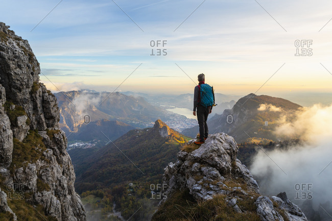 Pensive hiker looking at view while standing on mountain peak during sunrise at Bergamasque Alps- Italy
