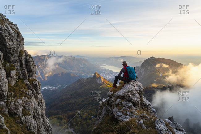 Pensive hiker looking at view while sitting on mountain peak during sunrise at Bergamasque Alps- Italy