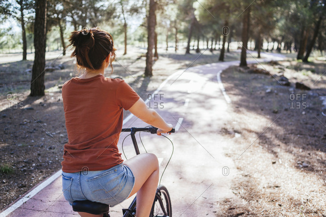 Woman riding bicycle at countryside during sunny day