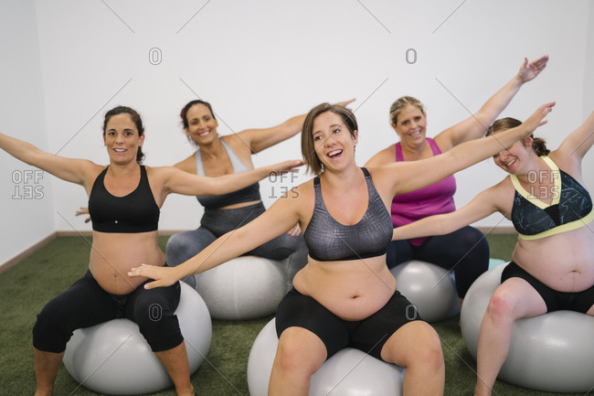 Happy pregnant woman with arms outstretched sitting on fitness ball