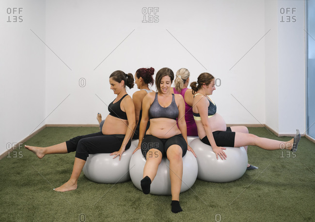 Pregnant woman sitting on fitness ball in round circle with leg up at yoga studio