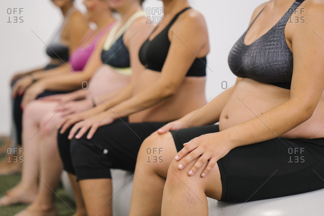 Midsection of pregnant woman sitting on fitness ball