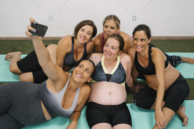 Smiling group of pregnant woman taking selfie on smart phone while sitting at yoga studio