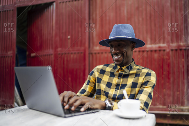 Smiling man using laptop at table against red metallic structure