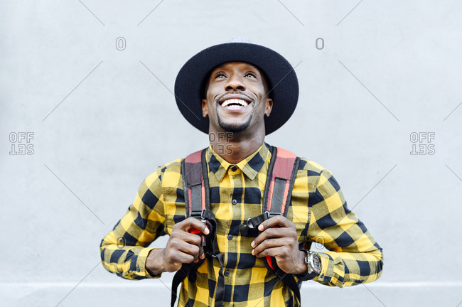 Smiling african man with backpack in hat looking up against white wall