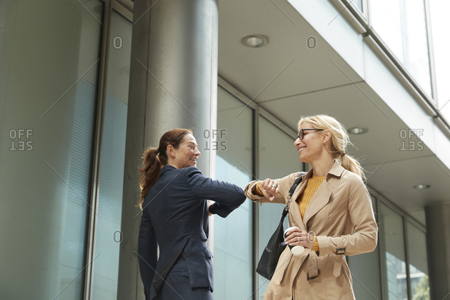 Businesswoman and colleague greeting with elbow bump while standing in city
