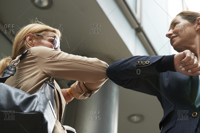 Smiling colleagues greeting with elbow bump while standing in city