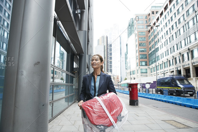 Smiling businesswoman holding shopping clothes while walking on street in city