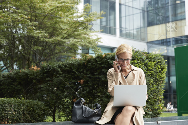 Businesswoman talking on mobile phone while working on laptop at office park