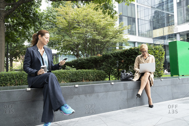 Businesswomen maintain social distancing while sitting at office park
