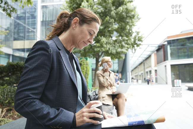 Businesswomen reading paper while colleague talking on mobile phone and using laptop in background at city