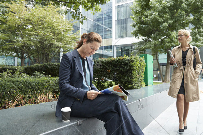 Businesswoman reading paper with colleague leaving after work at city