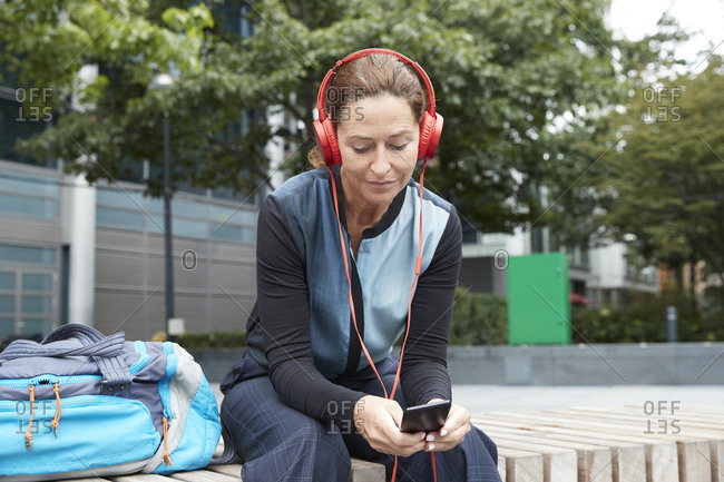 Businesswoman wearing business casual listening music while using phone in city