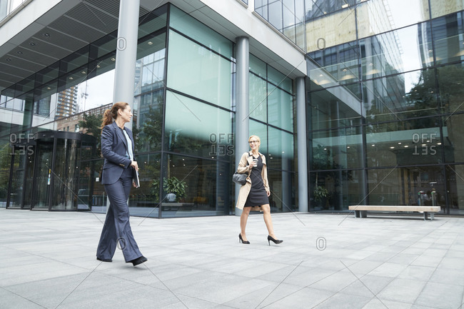 Colleague talking while walking against office building exterior