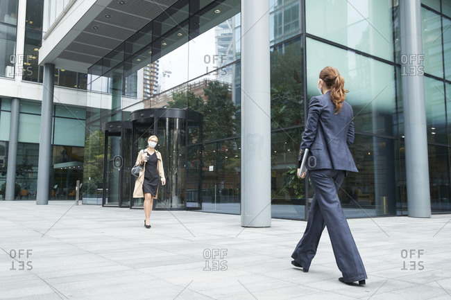 Business people wearing face mask while walking against office building
