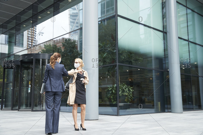 Business people wearing face mask greeting with elbow bump against office building